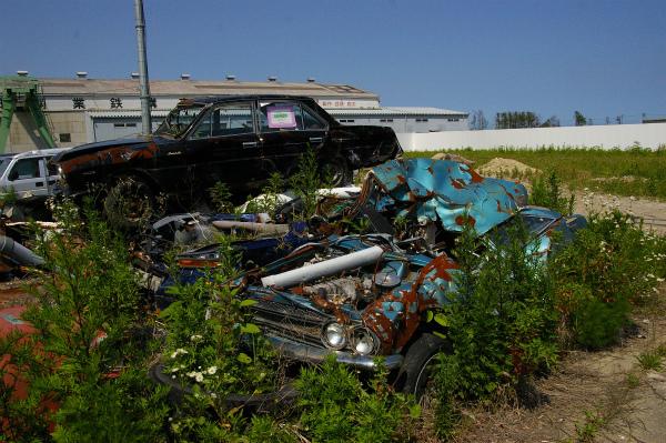 一年前と同じ場所に置かれたままのつぶれた車